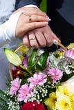 Mains de mariée et de marié sur le bouquet de mariage Image libre de droits