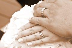 Mains de mariée et de mariés de jour du mariage avec des boucles Images stock