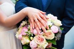 Mains de mariée et de marié avec des boucles de mariage Image libre de droits