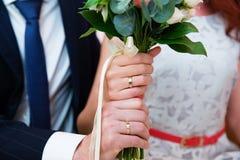Mains de mariée et de marié avec des boucles de mariage Images stock