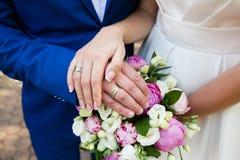 Mains de mariée et de marié avec des boucles de mariage Photos libres de droits