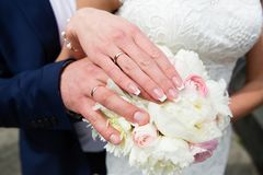 Mains de mariée et de marié avec des boucles de mariage Photo stock