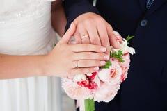 Mains de mariée et de marié avec des boucles de mariage Photo libre de droits