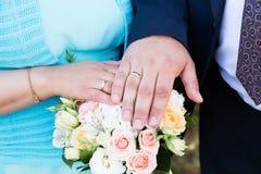 Mains de mariée et de marié avec des boucles de mariage Image stock
