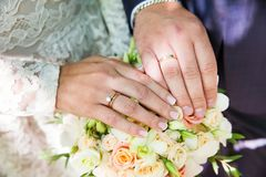 Mains de mariée et de marié avec des boucles de mariage Photos stock