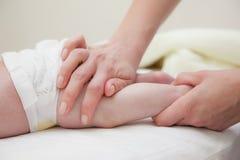 Mains de massage de jambes de bébé Image libre de droits