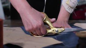 Mains de modèle de coupe d'ouvrière couturière avec des ciseaux banque de vidéos