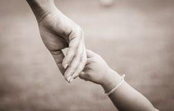 Mains de mère et d'enfant Image stock