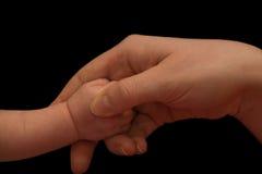 Mains de mère et de chéri sur le noir Image stock