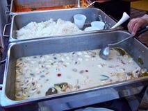 Mains de nourriture de portion de cuisinier à un événement approvisionné Photo libre de droits