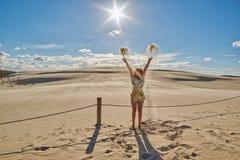Mains de ondulation de Madame rousse heureuse contre le coucher du soleil aux dunes de sable dedans Photos stock