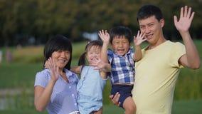 Mains de ondulation de famille asiatique heureuse ensemble dehors clips vidéos