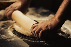 Mains de pâte de roulement de l'homme dans la cuisine images stock