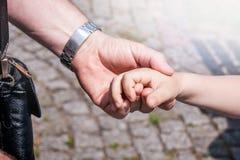 Mains de père et fils ou grand-père et petite-fille adultes Image stock