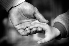 Mains de père et de fils tenant le moment Photo stock