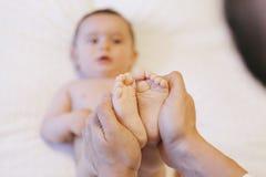 Mains de père tenant ses pieds nouveau-nés de bébé Photos stock