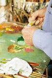 Mains de peintre avec le tube de peinture Photographie stock libre de droits