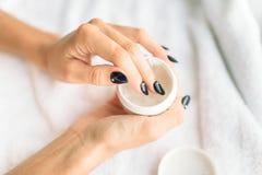 Mains de personne féminine avec le plan rapproché de produit de beauté Photographie stock libre de droits