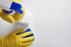 Mains de personnel de nettoyage avec des outils de nettoyage sur le dessus de table Images stock