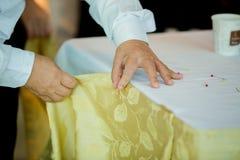 Mains de personnel préparant la nappe avec la goupille et les décorations photos libres de droits