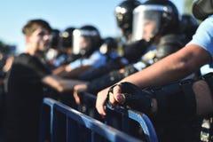 Mains de personnel de sécurité sur une barrière de protection pendant une émeute photo stock