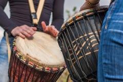Mains de personnes jouant la musique aux tambours de djembe Image stock