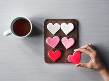 Mains de personnes montrant des biscuits de forme de coeur avec la tasse de café Photographie stock
