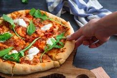 Mains de personnes prenant des tranches de pizza Margherita Fond noir Image stock