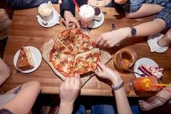 Mains de personnes prenant des tranches de pizza Margherita Margarita et mains de pizza Images stock
