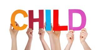 Mains de personnes tenant l'enfant droit coloré de Word Images libres de droits