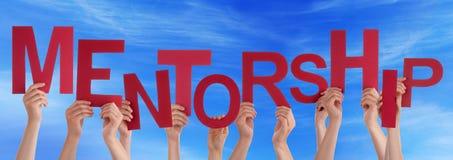 Mains de personnes tenant le ciel bleu de Mentorship rouge de Word Photographie stock libre de droits