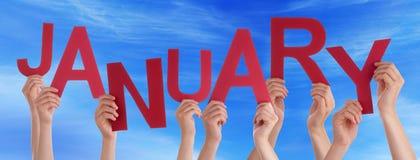 Mains de personnes tenant le ciel bleu rouge de Word janvier Image stock