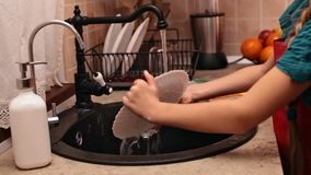 Mains de petite fille lavant un plat banque de vidéos