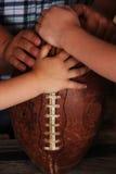 Mains de petits garçons sur le football Images libres de droits