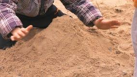 Mains de peu d'enfant jouant avec le sable banque de vidéos