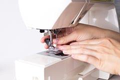 Mains de pied de réparation femelle de machine à coudre photographie stock libre de droits