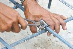 Mains de pince d'utilisation d'ouvrier pour la tige de tricotage en métal Image stock
