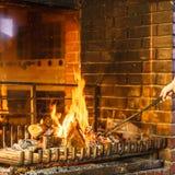 Mains de plan rapproché avec le tisonnier de fer de feu à la cheminée images stock