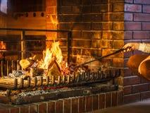 Mains de plan rapproché avec le tisonnier de fer de feu à la cheminée photographie stock libre de droits