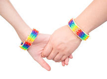 Mains de plan rapproché avec un bracelet modelé comme drapeau d'arc-en-ciel D'isolement sur le blanc Photographie stock