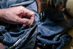 Mains de plan rapproché d'homme de tailleur travaillant à la vieille machine à coudre textile de tissu de tissu de jeans dans le  photographie stock