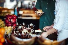 Mains de plan rapproché de buffet de gâteau au fromage d'invité de festins de chef Image stock