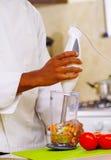 Mains de plan rapproché de chef mélangeant ensemble les légumes colorés en verre transparent utilisant le mélangeur tenu dans la  Photographie stock libre de droits