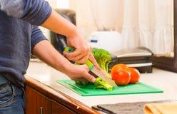 Mains de plan rapproché de l'homme utilisant le chandail bleu coupant des légumes sur la table de cuisine Photos libres de droits