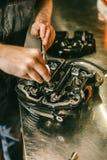 Mains de plan rapproché de la réparation de moteur de mécanicien de moto à la station service Photos stock