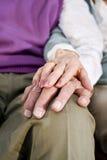 Mains de plan rapproché des couples aînés se reposant sur le genou Image stock