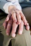 Mains de plan rapproché des couples aînés se reposant sur le genou Images libres de droits