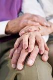 Mains de plan rapproché des couples aînés se reposant sur le genou Images stock