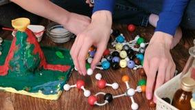 Mains de plan rapproché des modèles de molécule de bâtiment de maman et de fils d'ensemble en plastique coloré de construction banque de vidéos