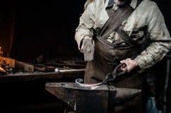 Mains de plan rapproché de la forge de village, tirant l'articl métallique Images libres de droits